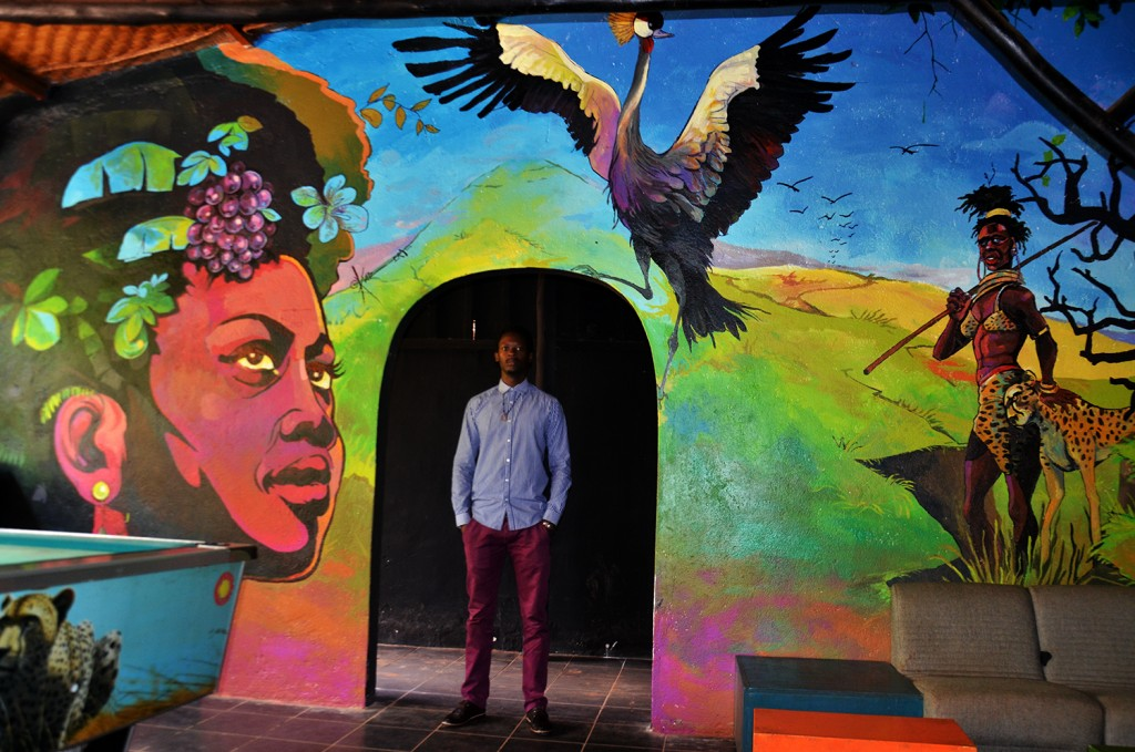 Kwizera stands in front of his mural painting at Iguana, where he also has his studio.