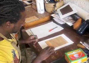 Henry Mzili Mujunga showing a printmaking technique (image : Start journal http://startjournal.org/2011/02/how-to-do-woodcut-printmaking-using-a-dark-to-light-technique/)